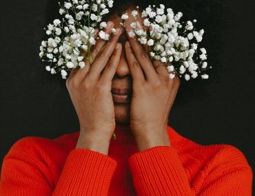 person in red long sleeve shirt holding white flowers